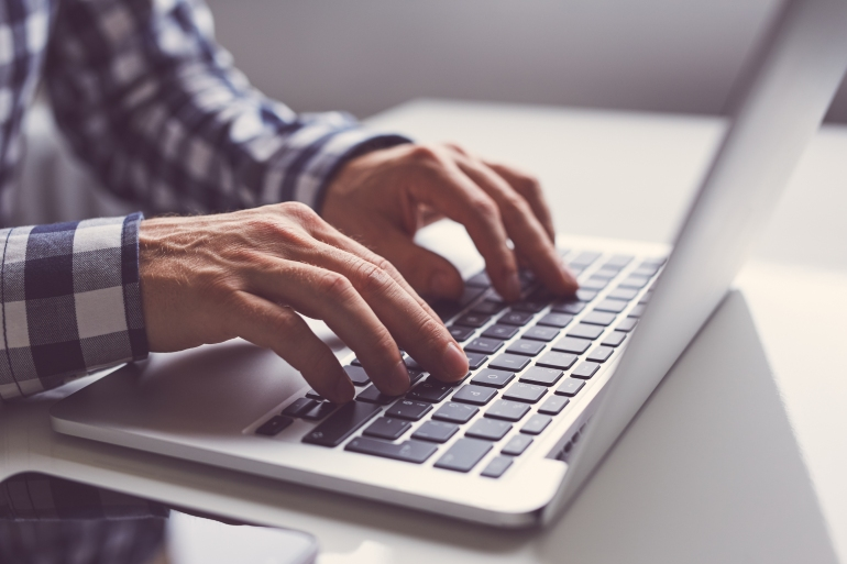 Man using laptop to writer better content for SEO in Japanese