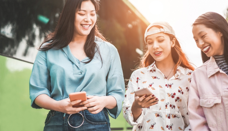 Happy friends using smartphones and enjoying Japanese PPC ads