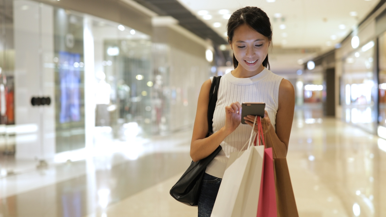 Tech savvy shopper using mobile ecommerce in Japan while shopping