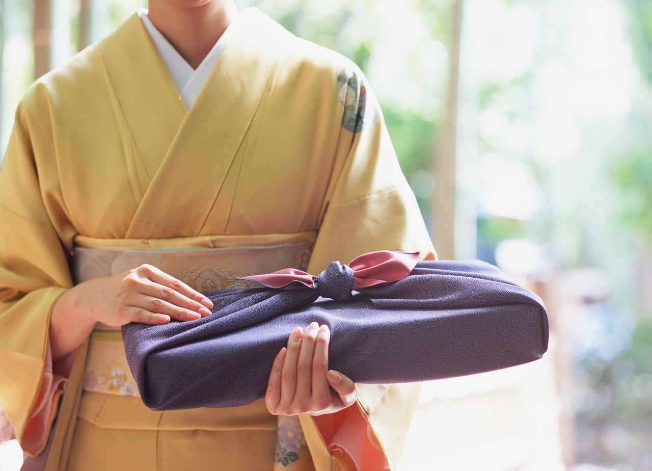 Woman holding gift and traditional item for Japanese holiday