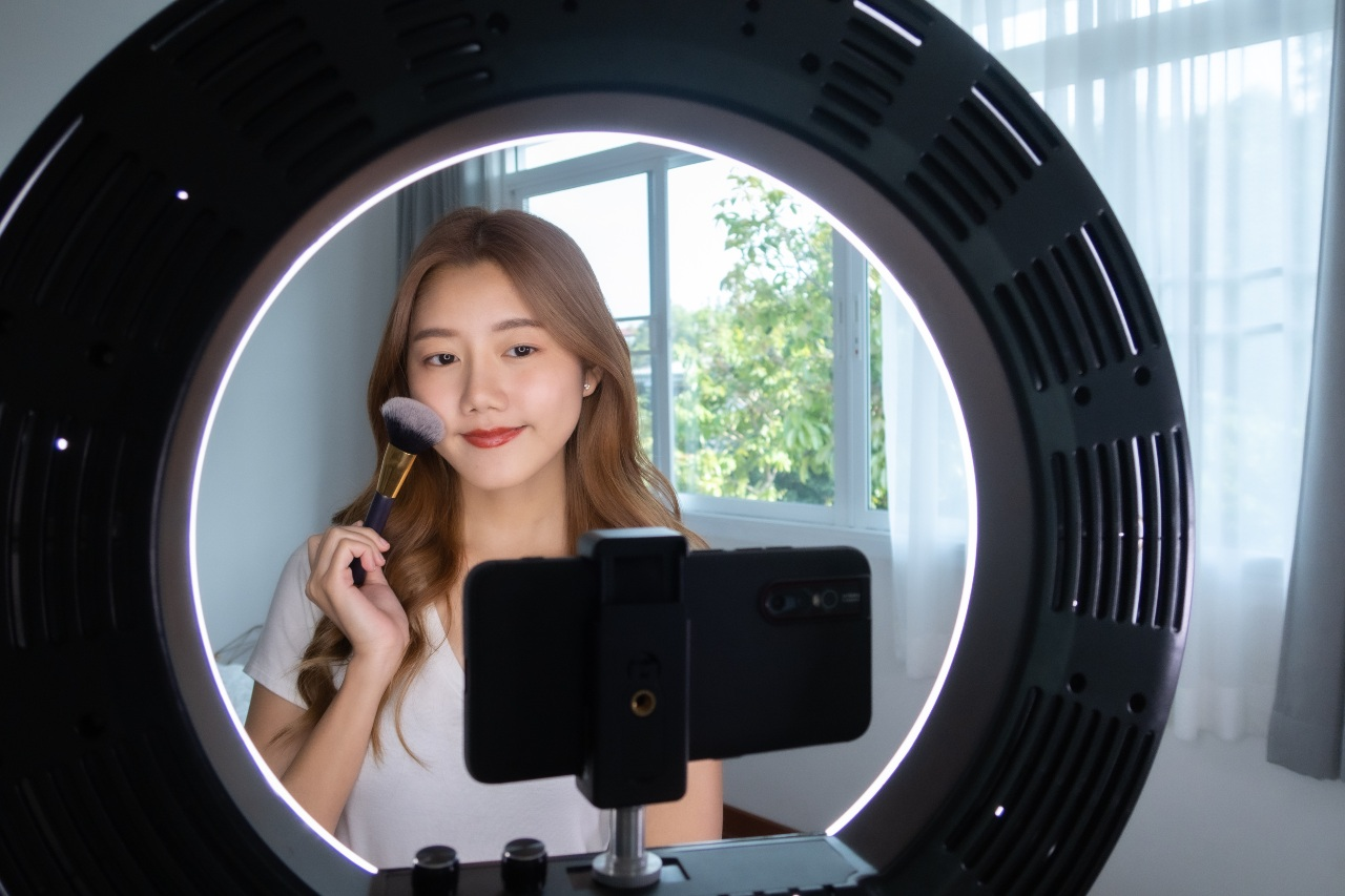 Woman influencer applying makeup for video TikTok ads in Japan