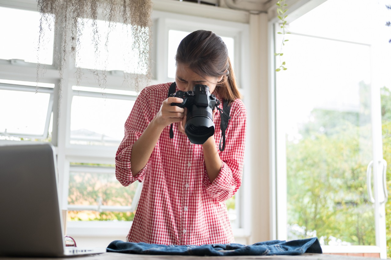 Woman taking photograph of jacket to sell on C2C ecommerce website in Japan