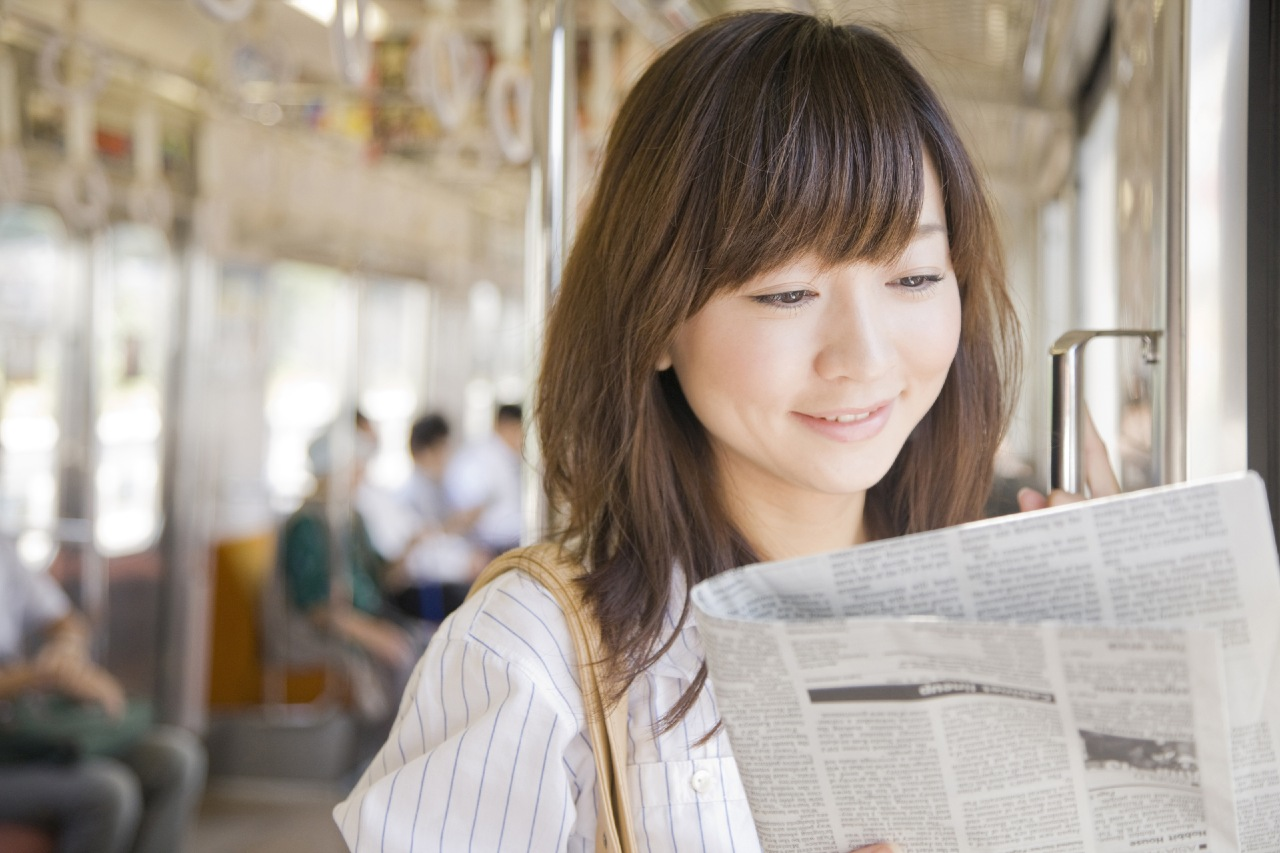 Woman on train reviewing promotional content released by PR agencies in Japan